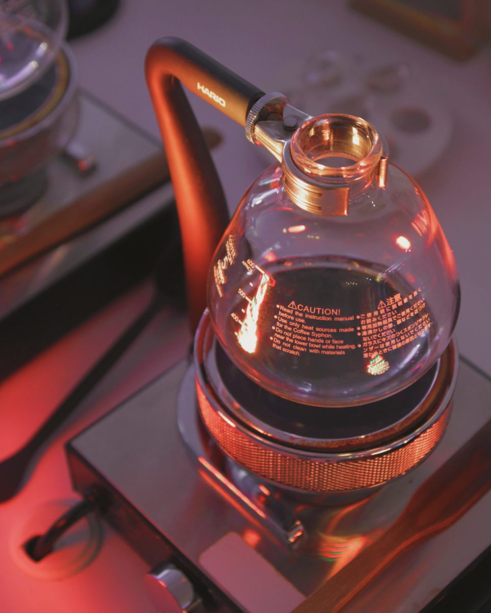 A siphon beaker sits on a heat lamp, sparkling in orange and purple light.