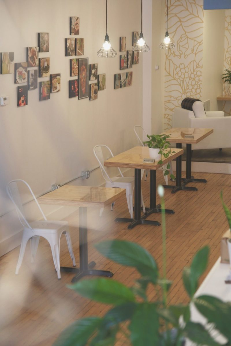 Distanced coffee seating in the shop with local art on the walls and vintage lights suspended from above.