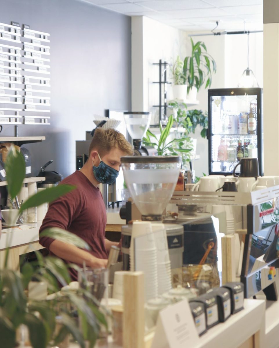A barista tends to the espresso machine in the coffee shop, full of light, plants, and whole beans.