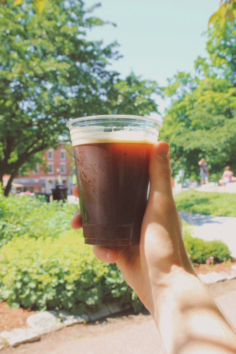 A hand holds a glass of cold brew coffee, illuminated by the sunlight in the park.